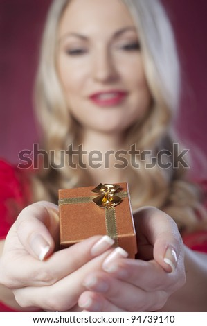 A beautiful young woman holding a gift on Valentines Day - stock photo