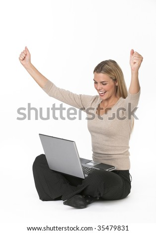 A beautiful young woman holding a laptop in her lap and cheering.  She has her fists raised in the air and has an excited expression on her face.  Vertically framed shot.