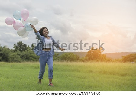 A beautiful young woman holding balloons , running along the pasture in the morning happily .