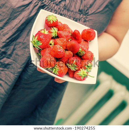 A beautiful young woman holding up a large bowl of fresh strawberries. Gorgeous slender young brunette woman indoors. - stock photo