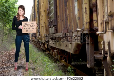 A beautiful young woman holding up a sign - stock photo