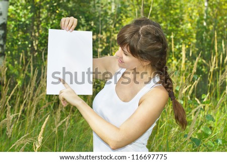 a beautiful young woman holds a blank white sheet of paper - stock photo