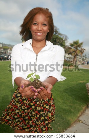 a beautiful young woman holds a green plant to represent earth friendly concepts - stock photo