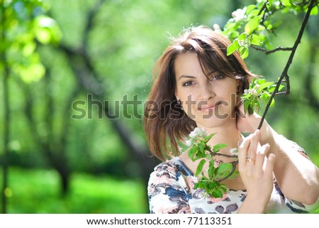 A beautiful young woman holds a tree branch - stock photo