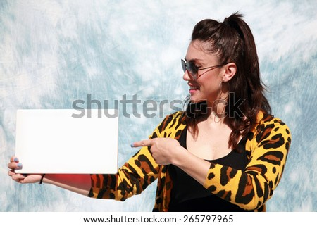 A beautiful young woman holds an blank Sign. Blank Signs are important in every building to lead the way outside especially in case of an emergency like a fire or flood or earthquake. - stock photo