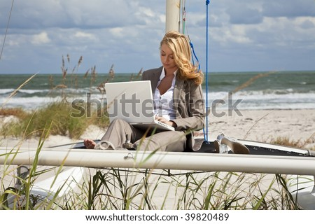 A beautiful young woman in a smart suit sitting barefoot on the deck of a small catamaran sailing boat using her laptop computer with the beach and sea behind her - stock photo