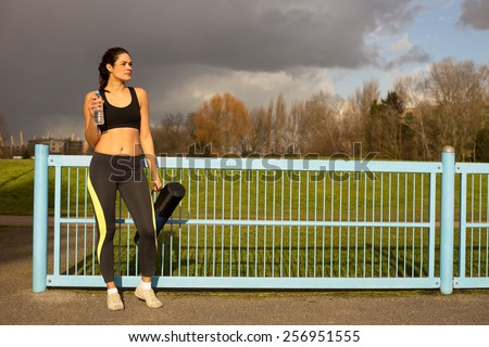 a beautiful young woman in fitness clothes with a bottle of water and gym mat.