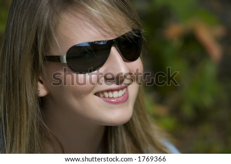 A beautiful young woman in sunglasses and with a big smile.