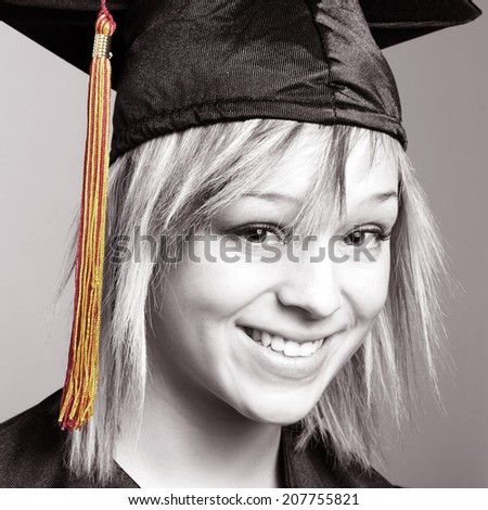 A beautiful young woman is happy to be graduating her school with a sense of an accomplishment. - stock photo