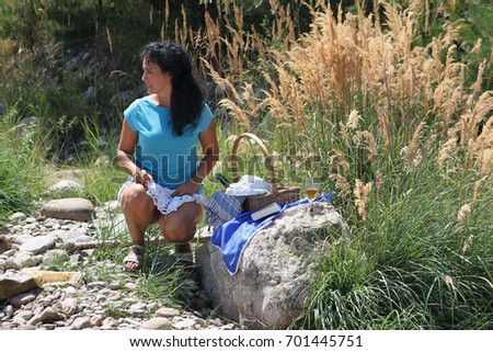 A beautiful young woman is having a picnic near the river
