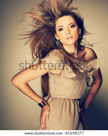 A beautiful young woman is in brown clothes - stock photo
