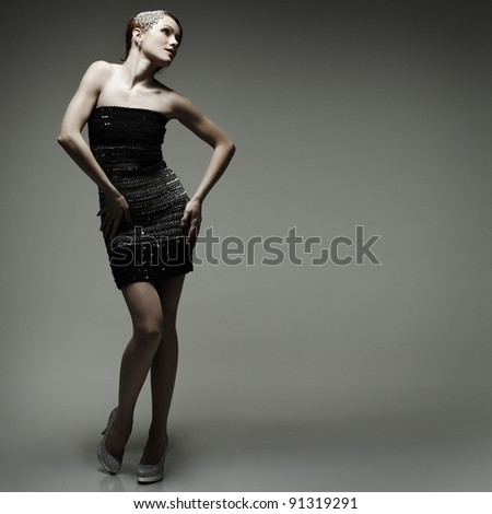 A beautiful young woman is in dark  clothes