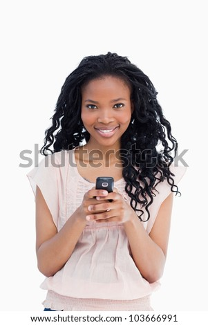 A beautiful young woman is looking at the camera and is holding a mobile phone