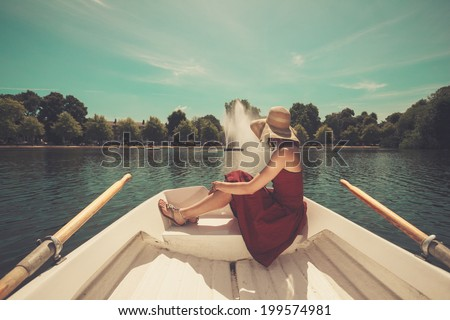 A beautiful young woman is relaxing in a rowing boat on a lake in the summer - stock photo
