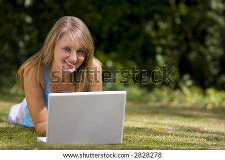 A beautiful young woman laying down in a grassy sunlit setting and working on her laptop