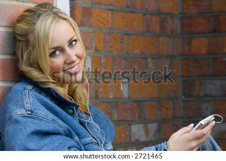 A beautiful young woman leaning against a wall and listening to an mp3 player