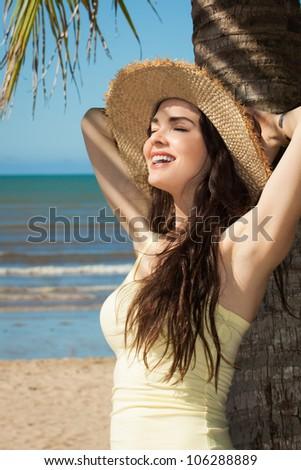 A beautiful young woman leaning against palm tree on a tropical beach wearing a straw hat. - stock photo