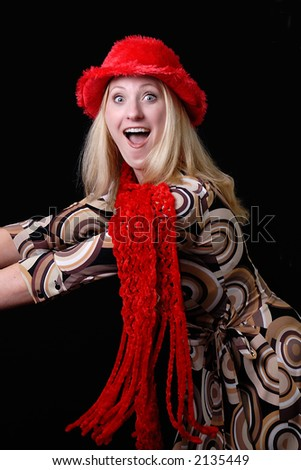 A beautiful young woman looks happy and surprised. She is wearing her red christmas scarf and hat. - stock photo