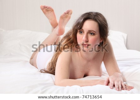 A beautiful young woman lying in bed, wearing only underwear briefs. She is lying on her front with feet up behind her, looking away. - stock photo