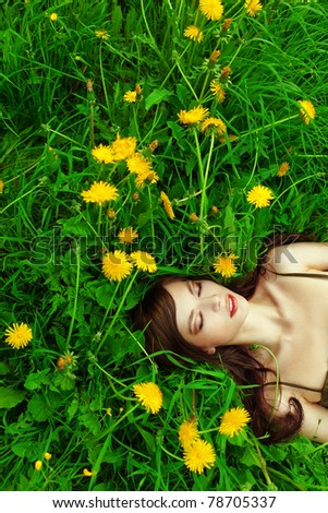 A beautiful young woman lying on the grass - stock photo