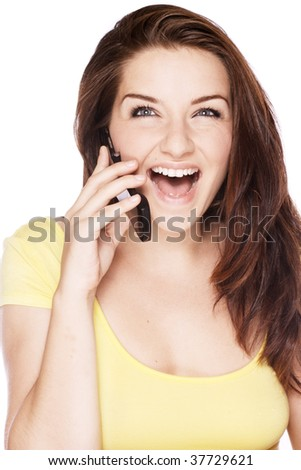 A beautiful young woman on her mobile phone and laughing on a white background.