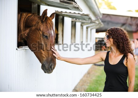 a beautiful young woman petting a horse - stock photo