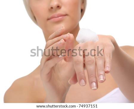 A beautiful young woman putting cream on her hands, focus on the hands