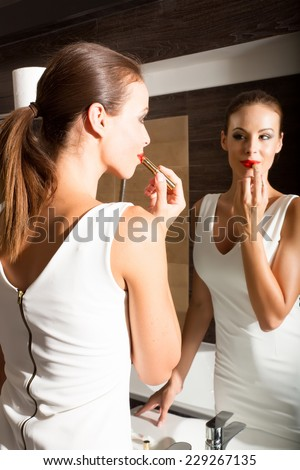 A beautiful young woman putting on makeup in the bathroom and getting ready to go out.  - stock photo