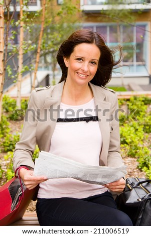 a beautiful young woman reading the newspaper.