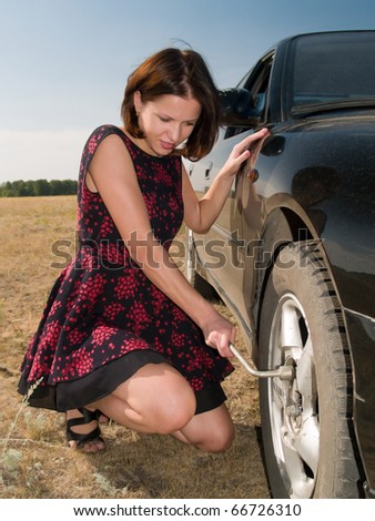 A beautiful young woman repairing a car, unscrew the wheel - stock photo
