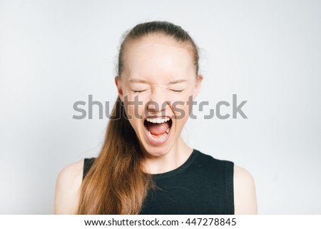 a beautiful young woman shouting angry, isolated on a gray background