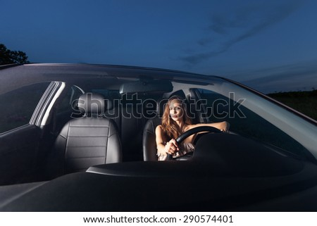 A beautiful young woman sits behind the wheel of the car and waiting passengers Outdoors - stock photo