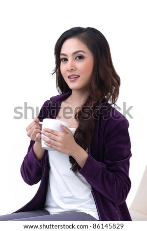 A beautiful young woman sitting and holding a cup of coffee - stock photo