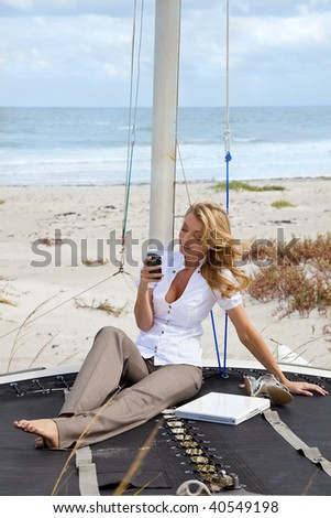 A beautiful young woman sitting barefoot on the deck of a small catamaran sailing boat using her smart phone to send a text with the beach and sea behind her