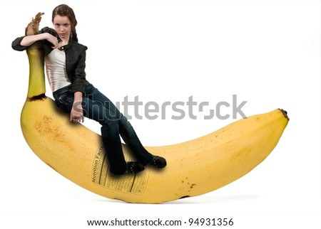 A beautiful young woman sitting on a banana with a nutrition label - stock photo