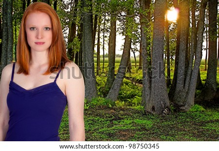 A beautiful young woman standing in a green forest in the early spring of the year. - stock photo