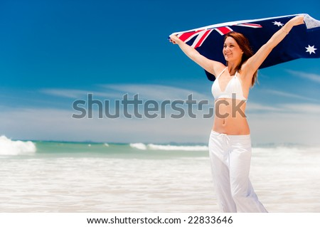 A beautiful young woman standing in the breeze with an Aussie towel - stock photo