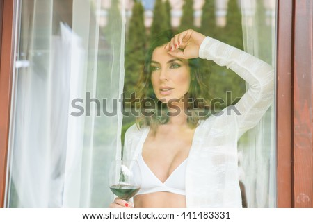A beautiful young woman standing in the window in underwear and enjoying a glass of wine. - stock photo