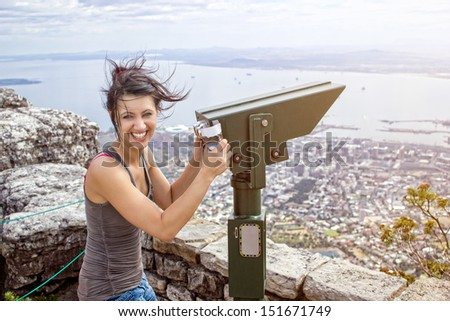 A beautiful young woman standing on table mountain with a big smile while she holds mountain binoculars. - stock photo