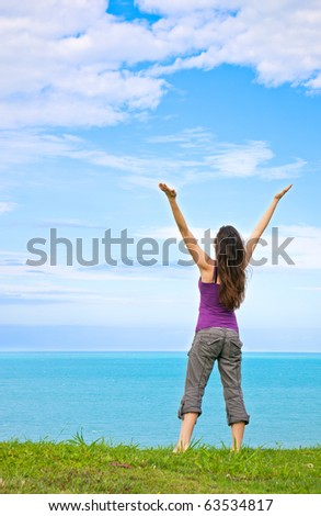 A beautiful young woman standing with her arms up in the air looking at the ocean
