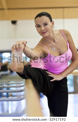 A beautiful young woman stretching on a bar at a dance studio