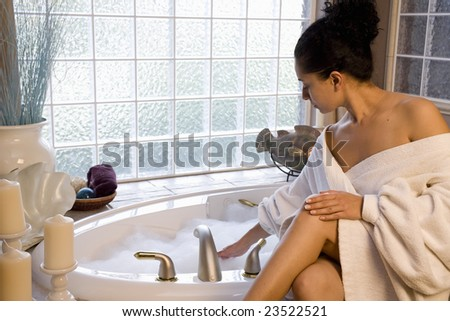 A beautiful young woman taking a bubble bath - stock photo