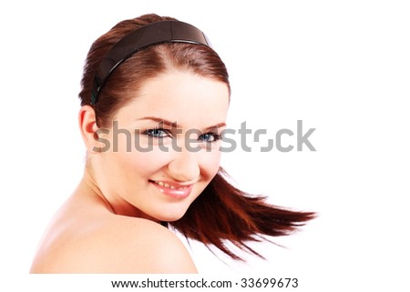 A beautiful young woman turning her head toward the camera and smiling.