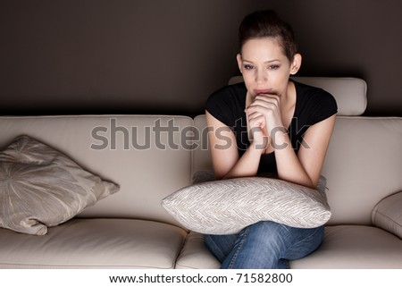 A beautiful young woman watching TV at home alone. - stock photo