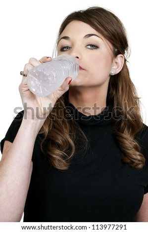 A beautiful young woman water from a plastic bottle - stock photo