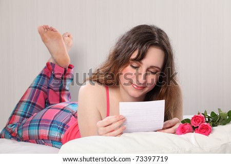 A beautiful young woman wearing pink pajamas, lying in bed reading a letter with three roses on the pillow. - stock photo