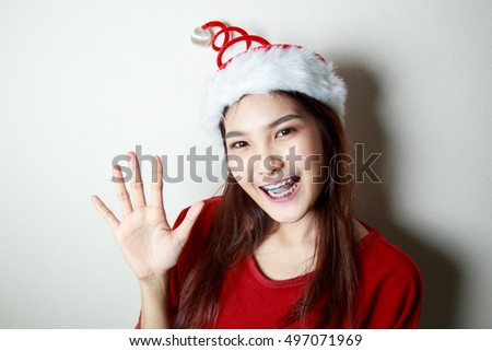A beautiful young woman wearing santa hat and smiling on  white background.