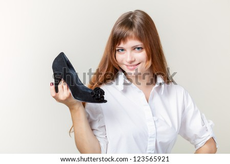 A beautiful young woman with a black shoe - stock photo
