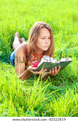 A beautiful young woman with an nectarine lying on the green grass and reading a book