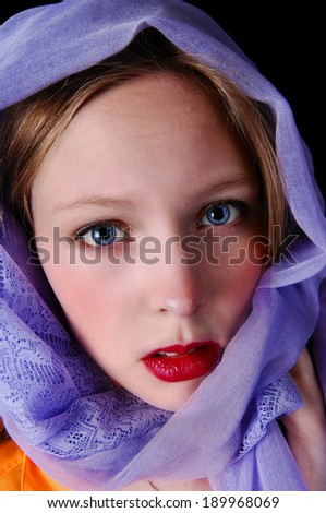 A beautiful young woman with blue eye's and a blue scarf around her head, isolated for black background.  - stock photo